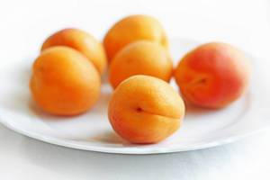 Close Up Bokeh Photo of Apricots on a White Plate