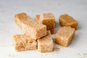 Close Up Bokeh Photo of Brown Sugar Cubes on White Table