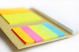 Close Up Bokeh Photo of Colorful Sticky Notes in a Notebook on white Background