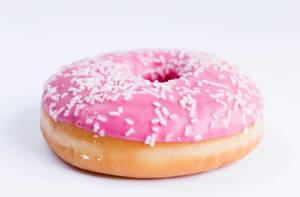 Close Up Bokeh Photo of pink donut with white sprinkles