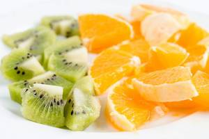 Close Up Bokeh Photo of Sliced Kiwi and Oranges on a Plate on White Background