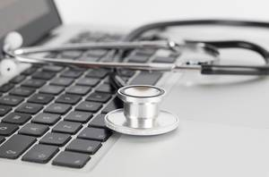 Close up Bokeh Photo of stethoscope laying on laptop keyboard