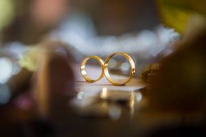Close Up Bokeh Photo of two Gold Wedding Rings standing on a Wedding Invitation Card