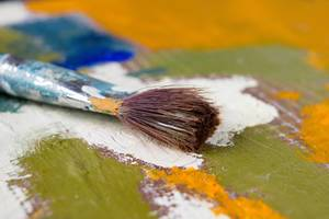 Close up brush on a colourful painted wooden surface
