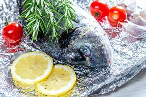 Close - up Dorado fish with rosemary, lemon slices and tomatoes on foil (Flip 2019)