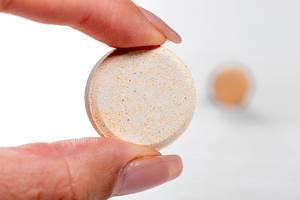 Close up einer bunten und runden Tablette in den Fingern einer Frau