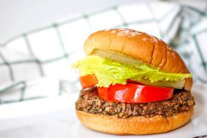 Close Up Food Photo of a Hamburger with Patty made from Beans, Tomato Slices and Lettuce on a White Plate with Kitchen Cloth in the Background