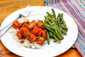 Close Up Food Photo of Asian Dish with Rice, Marinated Tofu and Green Beans on White Plate