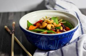 Close Up Food Photo of Asian Stir-Fried Vegetables with Cashew Nuts in Bowl next to Chopsticks on Wooden Table