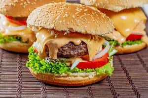 Close Up Food Photo of Burger with Beef Patty, Melted Cheese, Pickles, Tomatoes, Onions and Lettuce