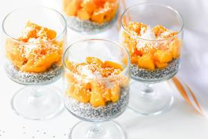 Close Up Food Photo of Chia Seed Pudding with Fresh Mango Cubes and Coconut Rasps in Glass Cups on White Background