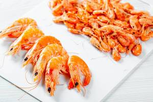 Close Up Food Photo of different sized Boiled Shrimps on White Cutting Board