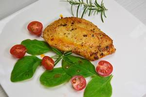 Close Up Food Photo of Grilled Chicken Breast with Cherry Tomatoes, Rosemary and Basil on white Plate
