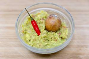 Close Up Food Photo of Guacamole Avocado Dip with Avocado Seed and Red Chili in Glass Bowl
