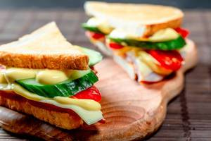 Close Up Food Photo of halved Ham Sandwiches with Melted Cheese, Cucumber and Tomato on a wooden Board