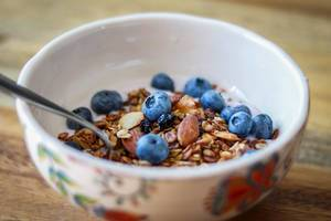 Close Up Food Photo of Healthy Granola Breakfast Bowl with Almonds and Blueberries in Ceramic Bowl on Wooden Table