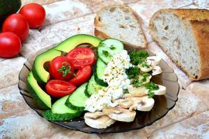Close Up Food Photo of Healthy Plate with Avocado, Cherry Tomatoes, Cucumber, Mushrooms and Fresh Bread