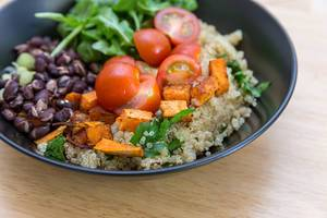 Close Up Food Photo of Healthy Vegan Bowl with Sweet Potatoes, Red Beans, Cherry Tomatoes and Arugula