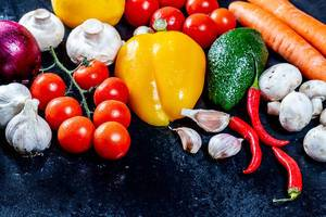 Close Up Food Photo of Healthy Vegetables such as Chili, Garlic, Bell Pepper, Cherry Tomatoes, Onion, Carrots and Mushrooms on dark background
