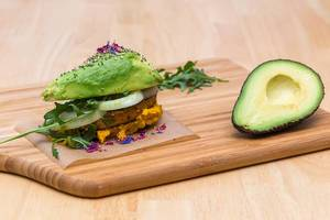 Close Up Food Photo of Home Made Vegetarian Avocado Burger with Hummus and Fresh Onion next to Halved Avocado on Wooden Cutting Board