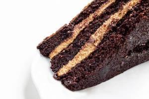 Close Up Food Photo of Homemade Chocolate Cream Cake Dessert on white Plate