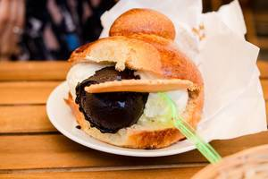 Close Up Food Photo of Ice Cream Sandwich Sicilian Brioche Bun stuffed with Ice Cream on Wooden Table