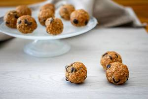 Close Up Food Photo of Oatmeal Energy Balls with Chocolate Chips on a White Wooden Table