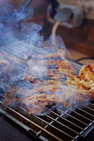 Close Up Food Photo of Pork Meat on a Barbecue Grill with Smoke around it