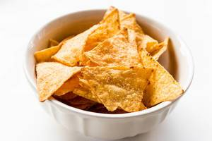 Close Up Food Photo of Seasoned Tortilla Cheese Chips in White Ceramic Bowl on White Background