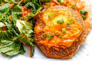 Close Up Food Photo of Sesame Cheese Bagel with Green Onions and Salad Side
