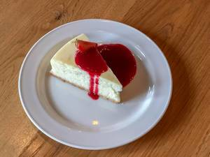 Close Up Food Photo of Slice of Cheesecake with Strawberry Sauce on a White Plate in Saint Petersburg, Russia