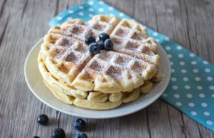 Close Up Food Photo of Stack of Waffles with Powdered Sugar and Blueberries on a White Plate
