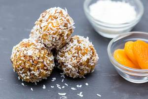 Close Up Food Photo of three desiccated Energy Balls next to a small bowl of Apricots and Yogurt