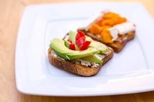 Close Up Food Photo of Toast with Cream Cheese, Avocado and Chili on White Plate