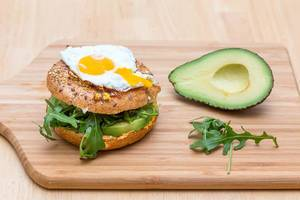 Close Up Food Photo of Vegetarian Avocado Burger with Arugula and Sunny Side Up Egg next to Halved Avocado on Wooden Cutting Board