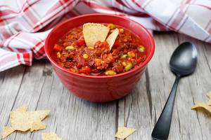 Close Up Food Photo of Vegetarian Chili with Bell Pepper, Corn and Beans on Wooden Table with Spoon
