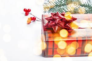 Close-up gift in red packaging with yellow bokeh. The concept of surprise for loved ones