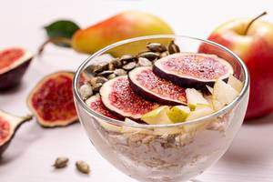 Close-up glass bowl of oatmeal with pieces of figs, pears, yogurt and pumpkin seeds (Flip 2019)