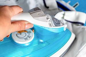 Close up hand of woman ironing clothes on ironing board