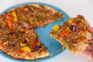 Close up knusprig gebackene vegetarische Pizza von Garden Gourmet in der Hand und bereit zum Verzehr