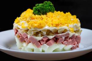 Close up layered salad with vegetables and ham on black background (Flip 2019)