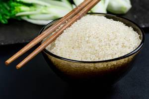 Close- up of a bowl of raw rice and chopsticks