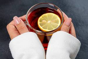 Close-up of a Cup of black tea with a piece of lemon in women