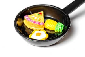 Close-up of a magnet toy frying pan with an egg, a piece of cake and a pineapple (Flip 2020)