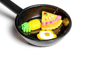 Close-up of a magnet toy frying pan with an egg, a piece of cake and a pineapple