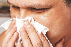 Close-up of a man with a runny nose holding a napkin near his nose (Flip 2019)