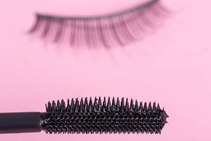 Close up of a mascara brush on a pink background with false lashes behind