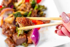 Close-up of a piece of baked beef in wooden chopsticks (Flip 2020)