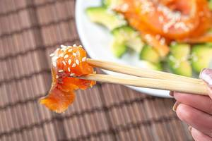 Close-up of a piece of smoked salmon with sesame seeds on chopsticks (Flip 2020)