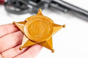 Close-up of a plastic toy police badge in hand